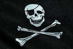 Fabric texture of the pirate flag waving in wind, calico jack pirate symbol, hacker and robber Royalty Free Stock Images