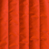 Fabric texture. Red orange quilted textiles with insulation. Vertical stripes.  Close up fragment of the top view Royalty Free Stock Image