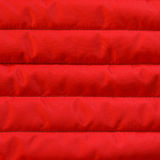Fabric texture. Red quilted textiles with insulation texture. Vertical stripes.  Close up fragment of the top view Royalty Free Stock Photography
