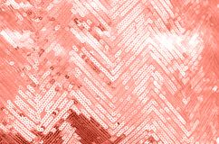 Fabric texture with shimmering coral sequins. Background with sequins. Fashionable color in 2019 stock images