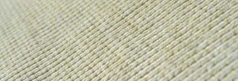 Fabric texture of a soft yellow knitted sweater. Macro image of the structure of bindings in yarns.  Stock Images