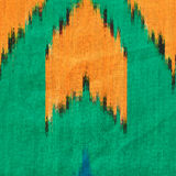 Fabric texture. Uzbek silk atlas Ikat. Orange, green and blue ornament. Close up fragment of the top view Royalty Free Stock Images