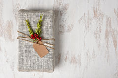 Fabric Wrapped Christmas Present. On a rustic whitewashed wood surface. Horizontal with copy space royalty free stock photography
