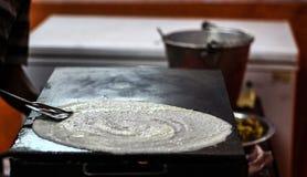 Fabricación de Dosa llano de papel en una cacerola del tawa separando la mezcla del dosa de arroz y de dal y engrasando en sheetM imagen de archivo libre de regalías