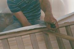 Fabricación de la canoa de la lona, estiramiento de lino en una canoa imagen de archivo