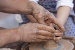 Fabricación de la cerámica Manos que trabajan en la rueda de la cerámica Foto de archivo