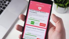 Fabricación de la donación de la caridad a la caridad del cáncer usando Smartphone App almacen de metraje de vídeo