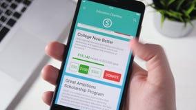 Fabricación de la donación de la caridad a la organización educativa usando Smartphone App almacen de video