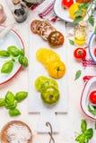Fabricación de la ensalada de los tomates Tomates maduros del verde, amarillos y rojos en la tabla de cortar de mármol blanca y e Foto de archivo libre de regalías