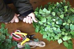 Fabricación de la escoba de abedul para el baño Las manos del ` s del hombre pusieron juntas ramas frescas de un árbol de abedul  Imágenes de archivo libres de regalías
