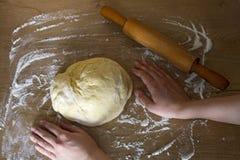 Fabricación de la pasta por las manos femeninas en fondo de madera de la tabla y un rodillo Imágenes de archivo libres de regalías