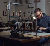 Fabricación de la ropa adapte sentarse en la tabla y el trabajo en una máquina de coser en el taller de costura fotos de archivo libres de regalías