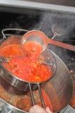 Fabricación de la salsa de tomate en la estufa Fotografía de archivo