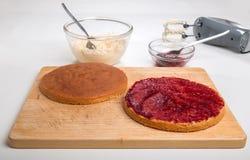 Fabricación de la torta de esponja, corte de la torta en la extensión de la mitad con el atasco Imagen de archivo