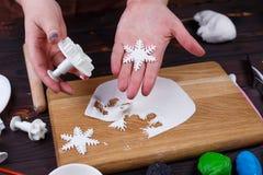 Fabricación de las decoraciones de la masilla de la confitería en la forma de copos de nieve fotos de archivo