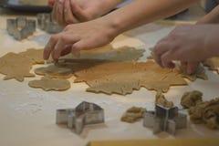 Fabricación de las galletas del pan de jengibre Cortadores de la pasta y de la galleta del fondo de la hornada de la Navidad fotografía de archivo