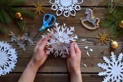 Fabricación de los copos de nieve de papel con sus propias manos Children& x27; s DIY Concepto de la Feliz Navidad y del Año Nuev foto de archivo libre de regalías