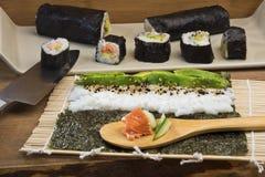 Fabricación de los rollos de sushi del maki Imagenes de archivo