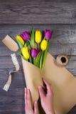 Fabricación de un ramo de tulipanes amarillos y púrpuras Imagen de archivo libre de regalías