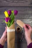 Fabricación de un ramo de tulipanes amarillos y púrpuras Imagen de archivo
