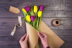 Fabricación de un ramo de tulipanes amarillos y púrpuras Imágenes de archivo libres de regalías