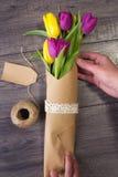 Fabricación de un ramo de tulipanes amarillos y púrpuras Fotos de archivo