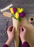 Fabricación de un ramo de tulipanes amarillos y púrpuras Imagenes de archivo