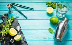 Fabricación del cóctel de Mojito Menta, cal, vidrio, hielo, ingredientes y coctelera en fondo de madera azul Imagenes de archivo