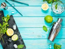 Fabricación del cóctel de Mojito Menta, cal, vidrio, hielo, ingredientes y coctelera en fondo de madera azul Visión superior Fotografía de archivo libre de regalías