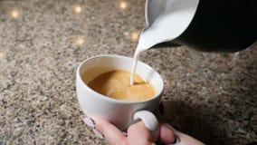Fabricación del café Barista Prepares Coffee Preparación del latte Barista que vierte la leche caliente en una taza de café expre metrajes