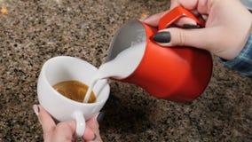 Fabricación del café Barista Prepares Coffee Preparación del latte Barista que vierte la leche caliente en una taza de café expre almacen de metraje de vídeo