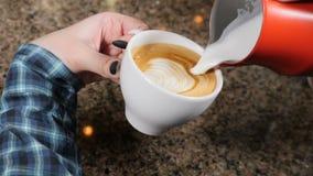 Fabricación del café Barista Prepares Coffee Preparación del latte Barista que vierte la leche caliente en una taza de café expre almacen de video