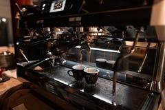 Fabricación del café con una máquina de café express Flujos deliciosos calientes del café express en dos tazas negras Tecnología  fotos de archivo libres de regalías