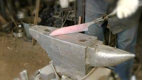 Fabricación del cuchillo fuera del metal en la fragua Ciérrese encima del golpe de las manos del ` s del herrero de fundición con almacen de metraje de vídeo