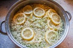 Fabricación del jugo de la baya del saúco con las rebanadas del limón fotografía de archivo