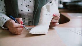 Fabricación hecha a mano de calzado El pegarse de la mujer escocés a la pluma de madera del último y de dibujo la silueta resbala metrajes