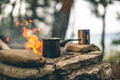 Fabricaci?n del caf? en cezve en la chimenea al acampar o el caminar caf? en hoguera imagen de archivo libre de regalías