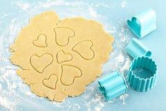 Fabricación de las galletas de torta dulce en forma de corazón con el cortador Imagenes de archivo