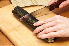 Fabricación de los rodillos de sushi. Imagen de archivo