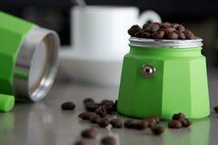 Fabricant d'expresso italien en vert avec les haricots et la tasse d'expresso Photographie stock libre de droits