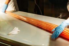 Fabricant de sucrerie roulant la sucrerie orange et blanche faite main de rayure à la main avec des gants en parc de Shiroi Koibi images stock