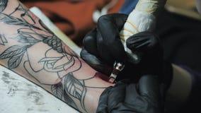 Fabricante da tatuagem da menina Artista que tattooing o homem novo Do porão locais no subsolo, tráfico de droga e crime Juventud video estoque