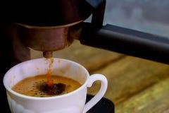 Fabricante de café con proceso de la taza de la fabricación en un café Fotografía de archivo libre de regalías