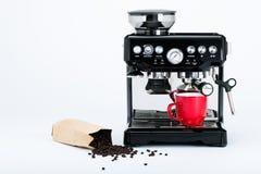 Fabricante de café manual negro aislado con la amoladora y la taza de café roja y bolso de los granos de café recientemente asado Fotos de archivo libres de regalías