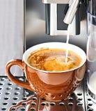 Fabricante de café que vierte el café fresco de la leche en una taza Foto de archivo libre de regalías
