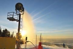 Fabricante de la nieve que hace nieve en la salida del sol en la montaña del urogallo Imagen de archivo libre de regalías