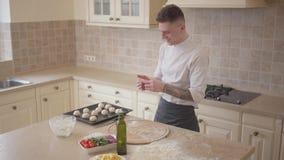 Fabricante de la pizza en el uniforme del cocinero que pone las bolas de la pasta para la pizza en la bandeja que cuece en la coc almacen de metraje de vídeo