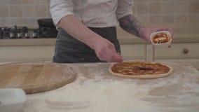Fabricante de la pizza que cocina la pizza en receta italiana tradicional Cocinero que hace la pizza italiana con las pastas del  almacen de metraje de vídeo