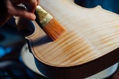 Fabricante del violín que barniza un cierre del cuerpo del violín para arriba Imágenes de archivo libres de regalías