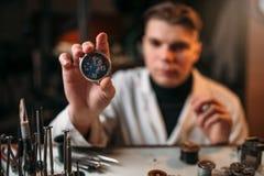 Fabricante do relógio que mantém o relógio de pulso disponivel imagem de stock royalty free